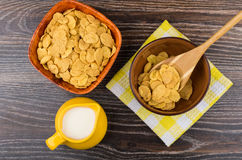 Corn flakes in bamboo bowl and jug milk on table Royalty Free Stock Photo
