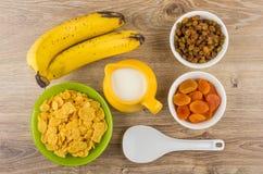 Corn flakes, bananas, jug milk, dried apricots, raisins and spoo Royalty Free Stock Photo