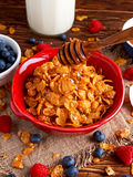 Corn Flakes with berries raspberries, blueberries, milk, and sweet pouring honey. Royalty Free Stock Photos