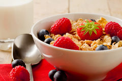 Corn flakes with berries on wooden table Royalty Free Stock Image