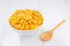 Corn flakes bowl with spoon on white wooden Stock Image
