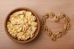 Corn flakes in bowl and walnuts royalty free stock photos