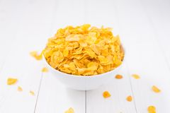 Corn flakes bowl on white wooden table Royalty Free Stock Image