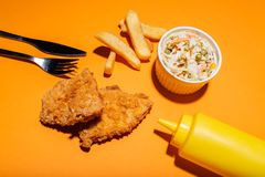 Corn flakes breaded fried chicken with mustard bottle, chips and salad placed on orange background. Food concept. stock photo