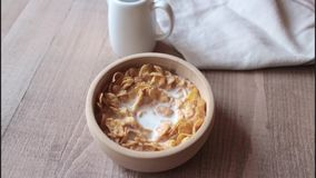 Corn flakes for breakfast. Corn flakes in a bowl pouring with milk stock video footage