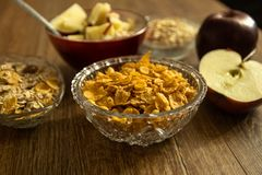 Corn flakes in a crystal bowl, fresh red organic apple and other healthy food royalty free stock photos
