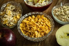 Corn flakes in a crystal bowl, fresh red organic apple and other healthy food royalty free stock photo