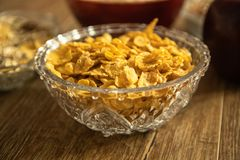 Corn flakes in a crystal bowl, fresh red organic apple and other healthy food royalty free stock photography