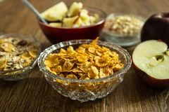 Corn flakes in a crystal bowl, fresh red organic apple and other healthy food royalty free stock image