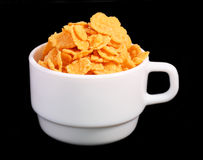 Corn Flakes in a Cup. Crispy corn flakes in a Cup. Black background Stock Photography