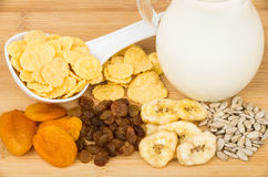 Corn flakes, dried fruits, sunflower seeds and milk Stock Images