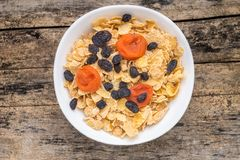 Corn flakes with dried fruits on wood background Royalty Free Stock Photography