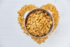 Corn-Flakes in einem Metall rollen auf einem gemalten weißen hölzernen Hintergrund Das Symbol des Herzens wird von den Corn-Flake stockfotografie