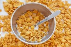 Corn-Flakes in einem Metall rollen mit Milch auf einem gemalten weißen hölzernen Hintergrund Corn-Flakes zerstreut auf einen Holz lizenzfreie stockfotos