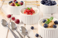 Corn flakes and fruit. Selective focus on the front cup with corn flakes and blueberries Stock Photos