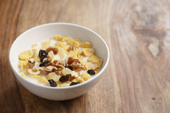 Corn flakes with fruits and nuts in white bowl on wood table with copy space Stock Photos