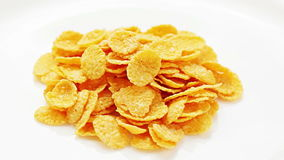 Corn flakes heap rotating on a white plate stock footage