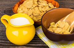 Corn flakes, jug milk and brown bowl on table Stock Image