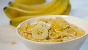 Corn flakes with milk are in a bowl. pieces of banana fall on the top of this delicious breakfast. Close-up shot.  stock video