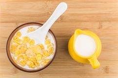 Corn flakes with milk in bowl and yellow jug Royalty Free Stock Photos