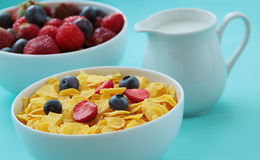 Corn flakes, milk and fresh fruits as blueberries and strawberries prepared for healthy breakfast. Close up view. Bowl of cornflakes, fresh fruits and milk Royalty Free Stock Photos