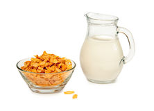 Corn flakes and milk. Corn flakes in a glass bowl and milk in glass jug isolated on white background Stock Images