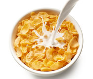 Corn flakes with milk. Pouring milk into bowl of corn flakes, top view Royalty Free Stock Photography