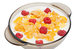 Corn flakes with milk and raspberry. In a black dish on a white background Royalty Free Stock Photos