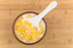 Corn flakes with milk and spoon in bowl on table Royalty Free Stock Photo