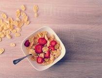Corn-Flakes mit Erdbeeren auf hölzernem Hintergrund Lizenzfreie Stockbilder