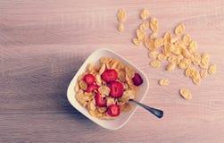 Corn-Flakes mit Erdbeeren auf hölzernem Hintergrund Lizenzfreie Stockfotos