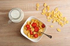 Corn-Flakes mit Erdbeeren und einem Krug Milch auf hölzernem backgro Lizenzfreie Stockbilder