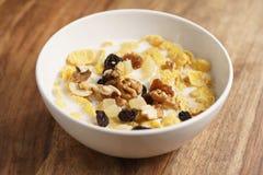 Corn Flakes mit Früchten und Nüssen in der weißen Schüssel auf hölzerner Tabelle Lizenzfreies Stockfoto