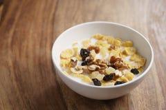 Corn Flakes mit Früchten und Nüssen in der weißen Schüssel auf hölzerner Tabelle mit Kopienraum Stockbilder