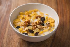 Corn flakes with nuts and fruits in white bowl on wood table Royalty Free Stock Photos