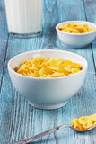 Corn flakes with raisin and milk in a ceramic cup. On a turquoise wooden surface Stock Photo