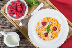 Corn flakes with raspberry and milk in plate. Crispy corn flakes with raspberry and milk in plate decorated with mint on wooden worktop, traditional and quick Stock Photography