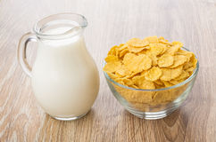 Corn flakes in transparent bowl and jug of milk Royalty Free Stock Photo
