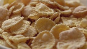 Corn flakes in white bowl. Close up view. Slide down. Corn flakes in white bowl with copyspace. Close up view. Slide down stock footage