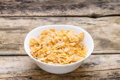 Corn flakes in white bowl on wood background Royalty Free Stock Photo