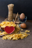 Corn flakes in wooden bowl with spoons and Red heart Royalty Free Stock Photography