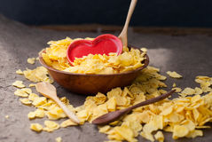 Corn flakes in wooden bowl with spoons and Red heart Royalty Free Stock Photos