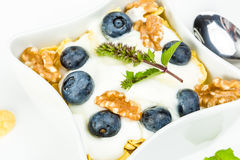 Corn flakes with yoghurt, honey, walnuts and blueberries Royalty Free Stock Photo
