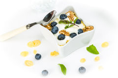 Corn flakes with yoghurt, honey, walnuts and blueberries Stock Image