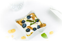 Corn flakes with yoghurt, honey, walnuts and blueberries Royalty Free Stock Images