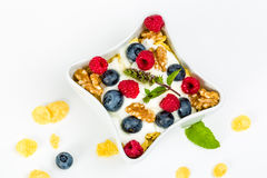 Corn flakes with yoghurt, honey, walnuts raspberries and blueber Stock Images