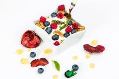 Corn flakes with yoghurt, honey, walnuts raspberries and blueber Stock Photo