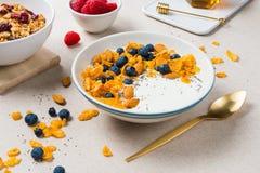 Corn flakes with yogurt, almonds, blueberries, raspberries and c stock photo