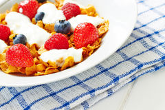Corn flakes with yogurt and berries on plate Stock Photos