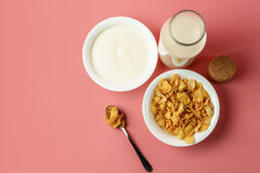 Corn flakes and yogurt in white bowl  with milk bottle. Place on pink background Royalty Free Stock Photos